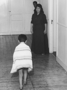 Ablutions in the Tibetan House.  A very young boy returns to his bedroom after a bath