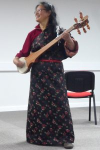 Former early Pestalozzi girl, Youdon, demonstrates her skill on the Tibetan lute during a presentation at Pestalozzi last week.